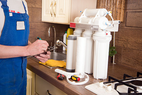 A technician in overalls fills out a document on a clipboard in front of a water filtration system that sits on a kitchen counter.