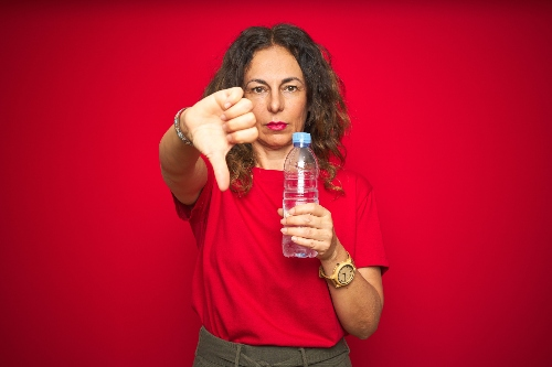 A woman has her thumb down while holding a water bottle.